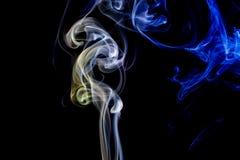 Abstracte blauwe en gele rook van de aromatische stokken Stock Fotografie