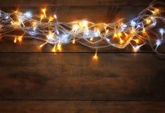 Abstracte foto van lichten van de Kerstmis de warme gouden slinger op houten rustieke achtergrond Gefiltreerd beeld Stock Afbeeldingen