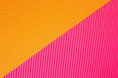 Abstracte geometrische document achtergrond in trillende oranje en roze in kleuren royalty-vrije stock foto's