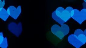 Abstracte lichten in de vorm van een hart op het zwart scherm De achtergrond van Bokeh Langzame Motie stock footage