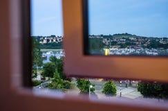 Abstracte mening die van een gedeeltelijk geopend hotelvenster, uit aan een beroemde Engelse rivier tijdens schemer kijken stock foto's