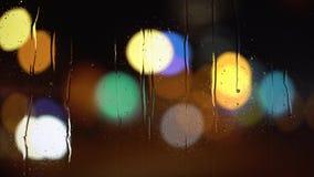 Abstracte onduidelijk beeldachtergrond van regenachtige stad bij nacht stock footage