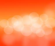 Abstracte oranje achtergrond met deeltjes, onduidelijk beeldzon. Royalty-vrije Stock Afbeelding