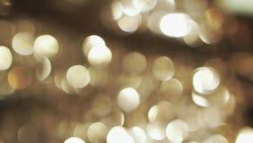 Abstracte schitterende gouden lichten, een echte geschotene video in het onduidelijke beeld stock video