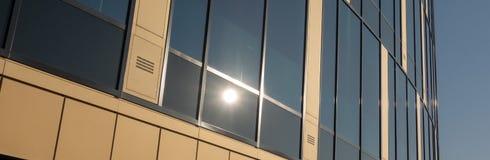 Abstracte sectie van een modern gebouw met een glas façade waarin de zon wordt weerspiegeld royalty-vrije stock fotografie