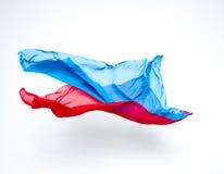 Abstracte stukken van het blauwe en rode stof vliegen Stock Fotografie