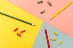 Abstracted é lápis e grampos coloridos em amarelo, verde, vermelho imagens de stock