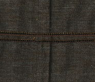 Abstraction for the background. dark brown fabric with the bulk seam. Closeup of brown with seam. Close up of brown  detail with white stitching. Brown canvas Royalty Free Stock Photography
