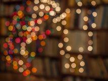Abstraction. Blurred colorful Christmas lights background over dark background with library. Abstraction stock photo