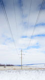 Abstraction of high-voltage wires. In a winter snow-covered field against a background of blue clear sky Stock Photos
