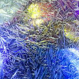 Abstraction. Ice flowers. Frost flowers. Frozen window. Winter in the window. Christmas lights in the window. Illumination. Royalty Free Stock Image