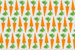 Abstraction of orange carrots with green shoots. Royalty Free Stock Photo