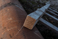 Abstraction of a rusty pipe and a pattern on a wooden staircase Royalty Free Stock Photography
