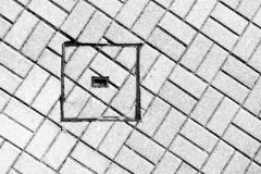 Abstraction of sewer manhole on floor with cobblestones Stock Photography