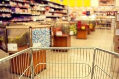 Abstraia a foto borrada da loja com trole do alimento em um supermark fotografia de stock