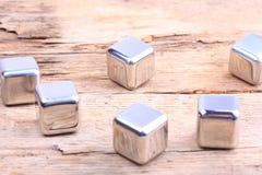 abstraia o fundo cubos de aço em uma superfície de madeira Imagem de Stock Royalty Free