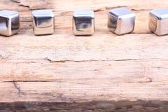 abstraia o fundo cubos de aço em uma superfície de madeira Imagem de Stock