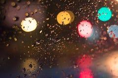 abstraiga el fondo Descensos sobre el vidrio en la noche con el bokeh foto de archivo libre de regalías