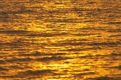 Abstrakcjonistyczna fotografia nawierzchniowa woda morze lub ocean przy zmierzchu czasem z złotym lekkim brzmieniem Obrazy Royalty Free