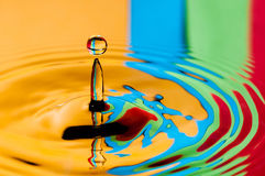 Abstrakcjonistycznego tła kolorowa wodna kropelka robi pluśnięciu Fotografia Royalty Free