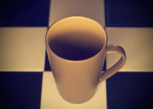 Abstrakcjonistycznego złocistego koloru brzmienia ceramiczny kubek na płytki tle obraz stock