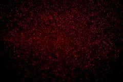 Abstrakcjonistyczny czerwony b?yskotliwo?? confetti b?yska na czarnym tle obrazy stock