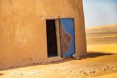 Abstrakcjonistyczny irrealny obrazek kąt dom w pustyni z otwartym błękitem uszkadzał drzwi żelazo, Sudan zdjęcia royalty free