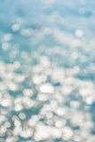 Abstrakcjonistyczny olśniewający światła słonecznego bokeh na błękitnym wody morskiej tekstury tle Zdjęcia Royalty Free
