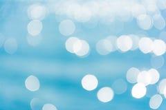 Abstrakcjonistyczny olśniewający światła słonecznego bokeh na błękitnym wody morskiej tekstury tle Zdjęcie Stock
