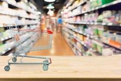 Abstrakcjonistyczny plama supermarket odkłada z wózek na zakupy na drewno stole fotografia stock