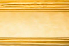 Abstrakcjonistyczny tło, draperii złota tkanina. Zdjęcia Stock
