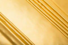 Abstrakcjonistyczny tło, draperii złota tkanina. Obraz Stock