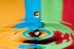 Abstrakcjonistyczny tło dwa kolorowej wodnej kropelki robi pluśnięciu Zdjęcia Royalty Free