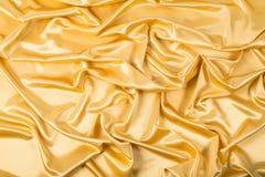 Abstrakcjonistyczny tło, draperii złota tkanina. Fotografia Stock