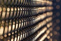 Abstrakcjonistyczny widok czarny łańcuszkowego połączenia ogrodzenie w wieczór świetle słonecznym Fotografia Stock