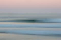 Abstrakcjonistyczny wschodu słońca oceanu tło z zamazanym panning ruchem Obrazy Stock