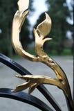 Abstrakcjonistyczny złocisty liść na dokonanego żelaza bramie Obrazy Stock