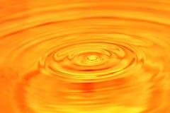 abstrakcyjny tło Kropla woda spada w złocie Zdjęcie Royalty Free