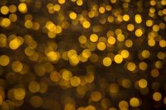 Abstrakt backgroung av guld- blänker och glöder glänsande ljus för mjuk bokeh Drömlik gnistrandebakgrund Arkivfoton