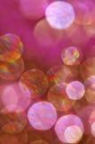 Abstrakt bakgrund av att sväva runda orbs i vibrerande magentafärgade, röda och guld- regnbågefärger Arkivfoton