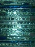 Abstrakt bakgrund av bunten av exponeringsglas i blått och gräsplan tonar med ljus bakifrån Arkivfoton