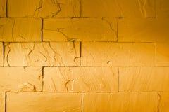 abstrakt bakgrund av den guld- tegelstenväggen Arkivbilder
