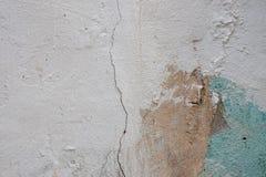 Abstrakt bakgrund av den vita strying väggen med sprickorna och bruna fläckar av målarfärg och grön färg Arkivfoto