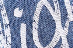 Abstrakt bakgrund av det vita typografiska trycket på den blåa t-skjortan Arkivfoton