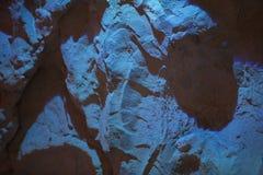 Abstrakt bakgrund av en stenvägg i ett ljust turkosljus Royaltyfria Foton