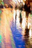 Abstrakt bakgrund av folkdiagram under paraplyer, stad i regn Ljusa reflexioner av lampor i våt trottoar Fotografering för Bildbyråer