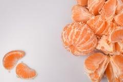 Abstrakt bakgrund av nya skalade mandariner: till rätten av en fruktglidbana till de vänstra två separata orange skivorna på ljus Royaltyfria Bilder