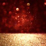 Abstrakt bakgrund av rött och guld- blänker bokehljus som är defocused Arkivbilder