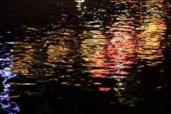 Abstrakt bakgrund av reflexionen av färgrikt ljus på vattenvåg på natten Arkivfoto