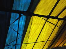Abstrakt bakgrund av remsorna av blått och guling med svart som delar slats Royaltyfri Foto